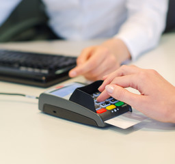 Female hand makes payment via bank terminal in office