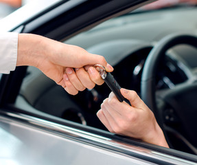 Closeup view of female hand inside the car getting keys