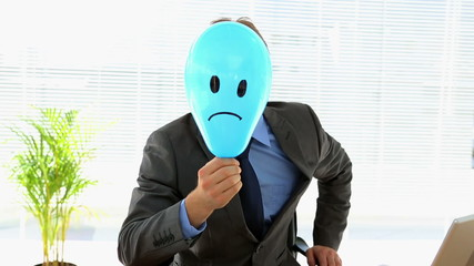Grumpy businessman holding sad face balloon over face
