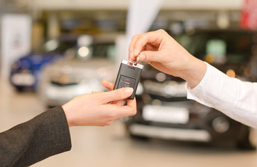 Female hand getting modern car key on several car background