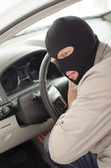 Thief in mask steals expensive new car.