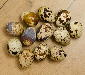 Few quail eggs on wooden tabletop.