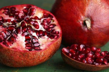 Ripe pomegranates on color wooden background
