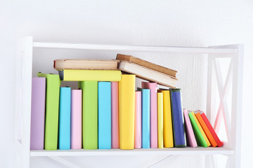 Books on white shelf in room