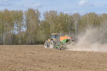 The tractor is engaged in the sowing of cereal crops in the fiel