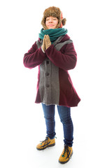 Young woman in warm clothing standing in prayer position