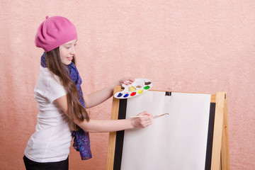 girl begins to draw picture on the easel