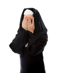 Young nun peeking through hands covering face