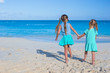 Two little cute girls enjoy their summer vacation on the beach