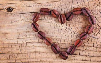 Coffee beans placed in shape of heart on old wooden background.