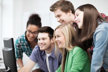 students looking at computer monitor at school