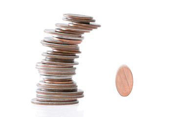 Precarious stack of coins falling