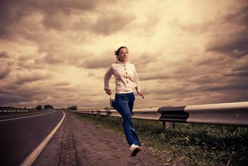 sportive woman running at freeway