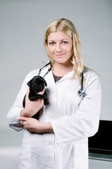 Young female blonde veterinarian holding a cute pug puppy