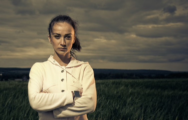 sportive woman portrait at stormy spring field