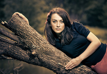 young woman on a fallen tree