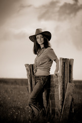 stylish cowgirl at wooden fence