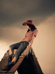 young woman in hat sitting on a top of wooden construction