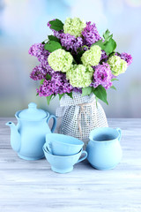 Composition with tea set and beautiful spring flowers in vase,