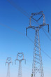 three high voltage pylons under blue sky