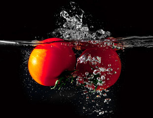 Two tomatoes falling into water