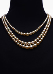 Yellow pearl necklace on black mannequin isolated on white