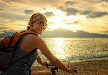 Young woman with backpack standing on the shore near his bike