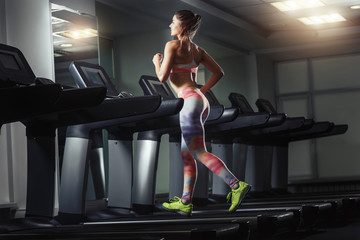 Young woman run on on a machine at the gym