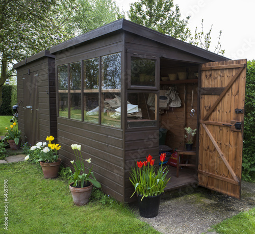 Garden shed with door open, tools, flowers, and plant pots. - 64651998