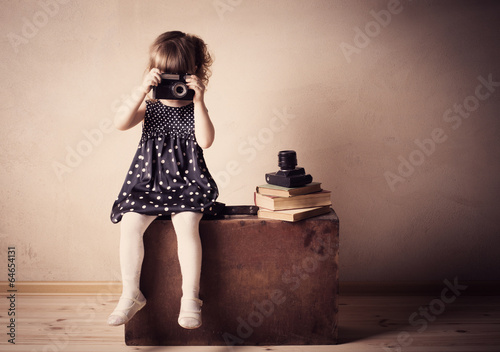 little girl with retro camera on  suitcase indoor