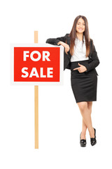 Woman pointing towards a for sale sign