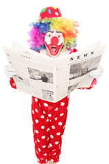 Surprised clown reading a newspaper