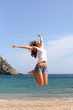 Funny woman jumping on a paradise beach
