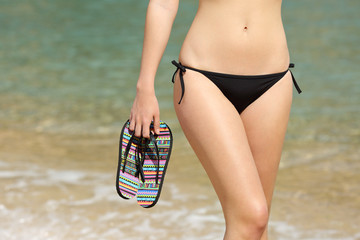 Close up of a woman hips holding flip flops on the beach