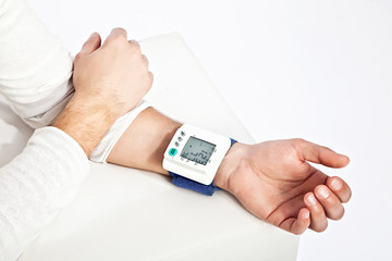 Photo of young man's hand measuring his blood pressure