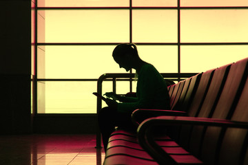 Silhouette of woman with tablet pc in the airport