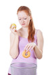 Girl choosing apple instead of a doughnut