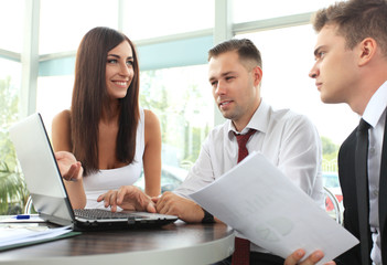 businesswoman pointing at document in laptop at meeting