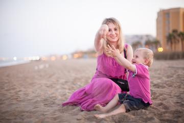 mama con su niño jugando con la arena