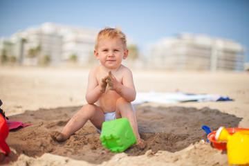 niño juega en la arena en la playa