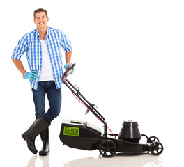 young man standing next to lawnmower