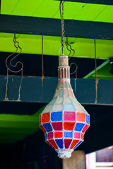 traditional color lamp hanging from a stucco wall