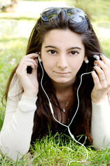 YOUNG GIRL WITH LONG BLACK HAIR LISTENING  MUSIC IN OUTDOOR