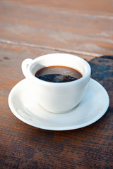 White porcelain cup of black coffee on wooden table. Outdoors