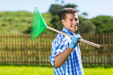 man with fan rake in home garden