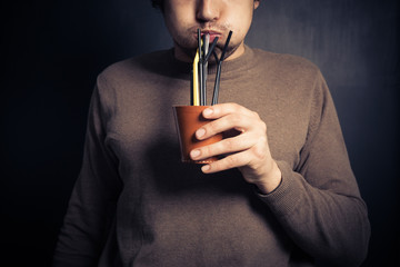 Silly young man drinking from leather cup with straws