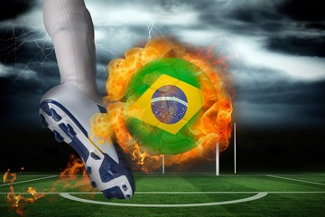 Football player kicking flaming brasil flag ball
