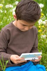 Junge beim Nintendo spielen im Garten 2