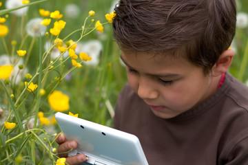 Junge beim Nintendo spielen im Garten