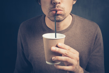 Young man drinking from paper cup with straw